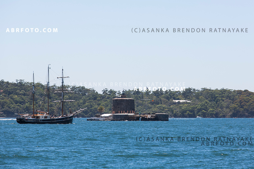 A old ship sails toward Fort Denison which is a former penal site and defensive facility occupying a small island located north-east of the Royal Botanic Gardens and about one kilometre east of the Opera House in Sydney Harbour, New South Wales, Australia. The island is also known as Pinchgut Island.