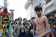 A young man is getting ready to start hitting himself with ceremonial knives during Ashura. AAshura commemorates a day of mourning for the death of Hussein ibn Ali, the grandson of the Prophet Muhammad, at the battle of Karbala.  Shias consider Hussein the third Imam and the rightful successor to Muhammad. The grief for his death is demonstrated by the self-flagellation. Lahore, Pakistan, 2009
