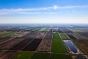 Nederland, Drenthe, Gemeente Borger-Odoorn, 01-05-2013; Tweederdeweg-Zuid gezien naar de lintbebouwing van Eerste Exloermond, Tweede Exloermond in de achtergrond. Rechts de overgebleven vloeivelden van de aardappelmeefabriek in Nieuw-Buinen. Veenkolonien, vlakverdeling van wijken en kanalen zoals resteerde nadat het turf steken in het hoogveen (vervening) gestaakt was.<br /> Fields on reclaimed peatland, to the right former flow fields (sewage fields) of the potato starch factory. At the horizon typical ribbon (linear) development of the villages.<br /> luchtfoto (toeslag op standard tarieven)<br /> aerial photo (additional fee required)<br /> copyright foto/photo Siebe Swart