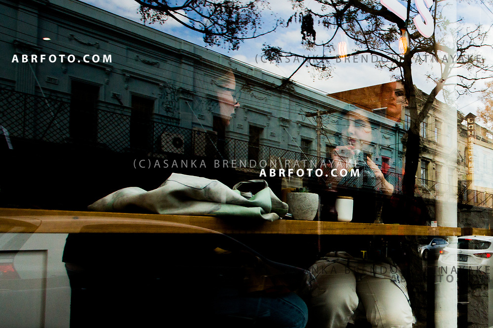 Highly sought after terrace houses are reflected onto a cafe window as diners sit inside on Gertrude Street Melbourne, Australia, September 1, 2017. The gentrification of the area of Fitzroy has resulted in a lot of members of the Aboriginal community moving to the outer suburbs of Melbourne. <br /> Asanka Brendon Ratnayake for the New York Times