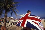 Man holding Union jack beach towel, walking along beach, Ibiza, 2000's,