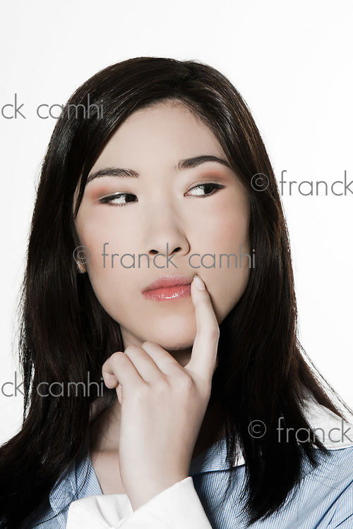 studio shot portrait of a beautiful southeast asian young woman pensive