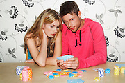 Young Couple playing cards looking at hand together