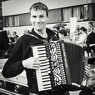 Man (Tom Solvi )with accordion playing in the parade from centrum of Leikanger to the bonfire  during Midsummer night festival