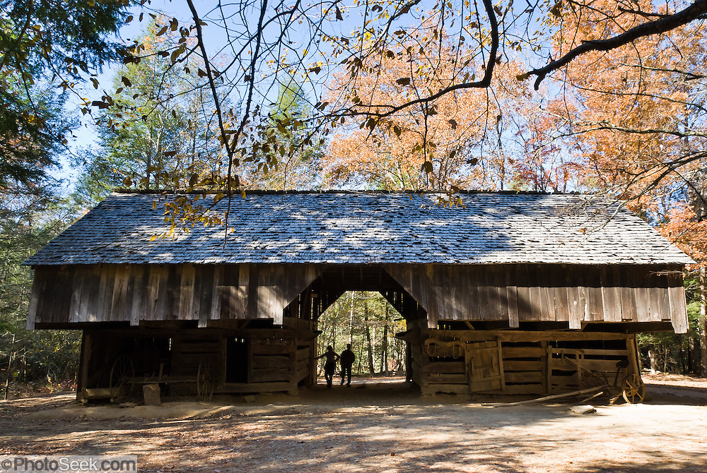 The overhang in cantilever barns provided shelter for animals and farm equipment. Cable Mill Historic Area, Cades Cove, Tennessee. Cades Cove, once home to numerous settlers, is an isolated valley located in Great Smoky Mountains National Park, USA. Today Cades Cove is the most popular destination for visitors to the park, attracting over two million visitors a year, due to its well preserved homesteads, scenic mountain views, and abundant display of wildlife.