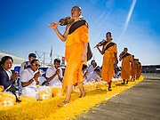 "02 JANUARY 2016 - KHLONG LUANG, PATHUM THANI, THAILAND:  Monks from the Dhammakaya sect walk through the crowd at Wat Phra Dhammakaya on the first day of the 5th annual Dhammachai Dhutanaga (a dhutanga is a ""wandering"" and translated as pilgrimage). More than 1,300 monks are participating pilgrimage through central Thailand. The purpose of the pilgrimage is to pay homage to the Buddha, preserve Buddhist culture, welcome the new year, and ""develop virtuous Buddhist youth leaders."" Wat Phra Dhammakaya is the largest Buddhist temple in Thailand and the center of the Dhammakaya movement, a Buddhist sect founded in the 1970s. The monks are using busses on some parts of the pilgrimage this year after complaints about traffic jams caused by the monks walking along main highways.         PHOTO BY JACK KURTZ"
