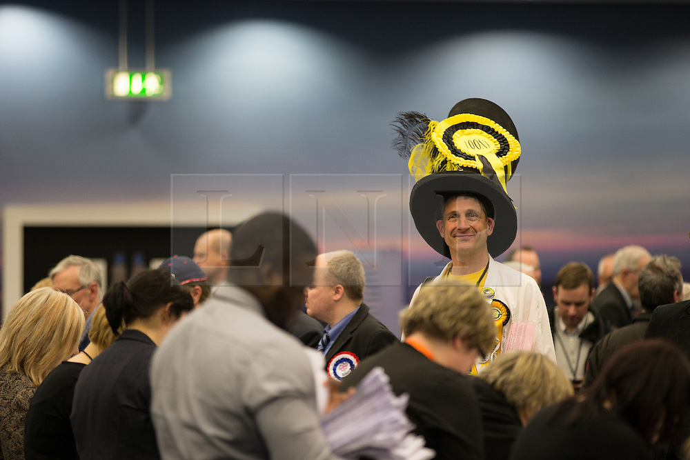 © Licensed to London News Pictures . 14/02/2014 . Manchester , UK . Monster Raving Loony Party election agent Nick Delves (aka The Flying Brick )  standing tall in the crowd in the counting hall . The count for the Wythenshawe and Sale East by-election , at Manchester Central this evening . Photo credit : Joel Goodman/LNP