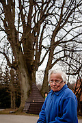 82 years old Vlasta Junkova - an inhabitant of Kunvald - is taking a short rest everytime she is passing the Limetree of Brethren. When in 1547 Jaroslav of Pernstejn forbade the activity of Unity of Bretheren, a lot of protestant families were forced to leave their motherland. As the legend says, upon leaving the Brethren used three small lime branches to dig out bits of the home soil for the memory. They planted these little branches afterwards. The huge limetree has grown from then. Its heights is about 40 m and its circumferenc is about 7 m in 1 m hight. The Unitas Fratrum (Brüdergemeine/Moravian Church) was founded in Kunvald in 1457, when followers of the martyred Jan Hus (John Huss) found refuge on the estate of King George of Poděbrady. Kunvald is a village in 5 km north of Žamberk in the Ústí nad Orlicí District, Pardubice Region of the Czech Republic. It has over 1,000 inhabitants.