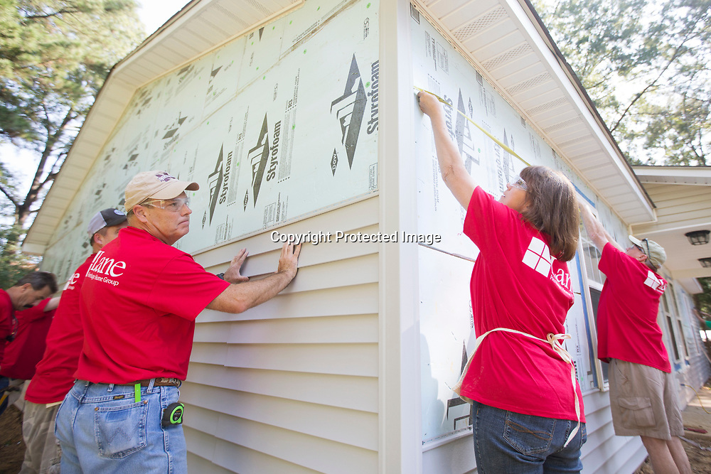 Bill Collins, left, and Janie Cobb, right, attach and measure siding as they and other Lane Furniture employees volunteer their time building a Habitat for Humanity home Friday morning in Verona.