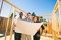 An African American couple looks at new home plans with contractor / architect in a home construction site...Model Releases: 20060726_MR_A = woman.20060726_MR_B = black man.20060726_MR_C = Caucasian man...Woman: 20060726_MR_A.