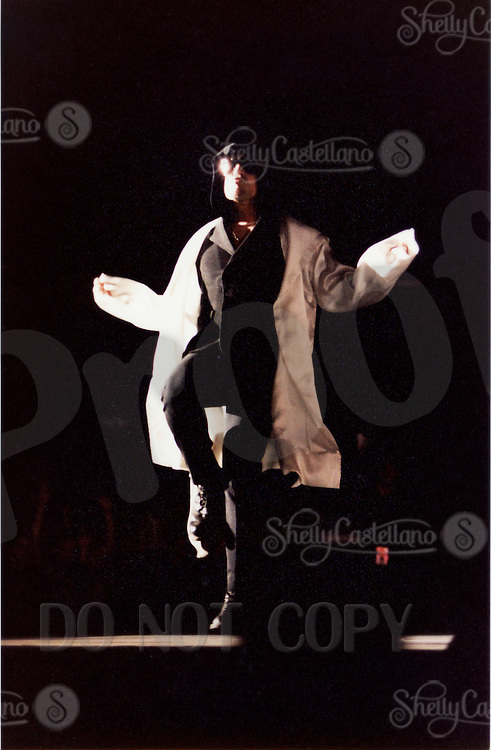 25 April 1997:  U2 lead singer BONO skipping an imaginary rope down the runway wearing a white hooded jacket and sunglasses entering the stadium during the U2 PopMart Tour in Las Vegas.  Photo ©1997ShellyCastellano.com  Print Scan. Roll / Negative # 3/6