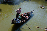 New York. Central park. gondolier and gondola, tourists rowing on the lake, skyline of central park  and the lake   / gondoles, touristes en barque ramant sur le lac, et la ligne des gratte ciel  et le lac  New york
