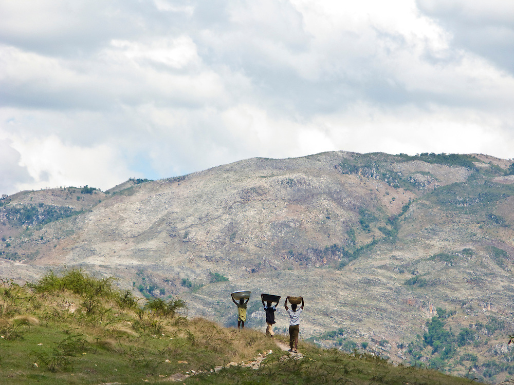 Three boys walk with deforested mountains in the background.
