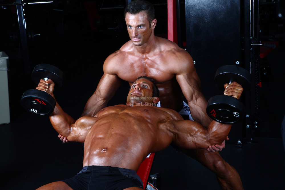 Bodybuilders Dan Decker and Brian Yersky doing chest workout with dumbbells on an incline bench.