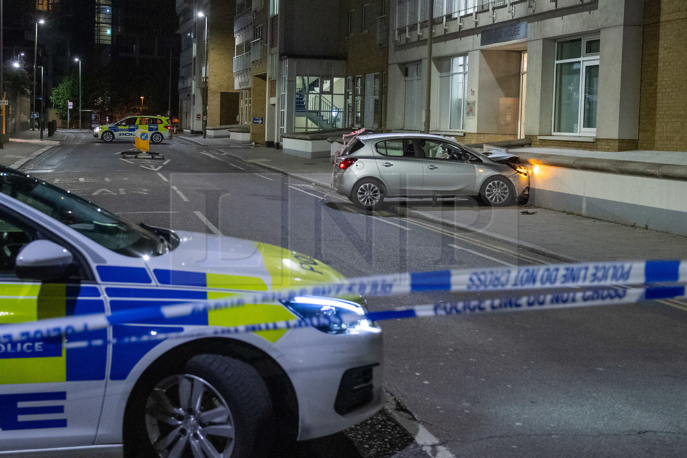 © Licensed to London News Pictures. 13/05/2020. London, UK. A police car forms a cordon in front of a vehicle that has collided with a wall on Lombard Street. Police were called at around 1800BST on Wednesday, 13 May, to reports of a man with a knife in Lombard Road, SW11. There were also reports of a car in collision with a wall in Lombard Road. Officers attended the location and found two men injured - one had cuts to his arms and the other cuts to his legs. Officers believed the two men had been travelling in the car. Both have been taken to hospital, where their injuries are not believed to be life-threatening. Investigations at the scene led officers to Vicarage Crescent, SW11, where they found two other injured men. Both were taken to hospital with non life-threatening injuries. Photo credit: Peter Manning/LNP