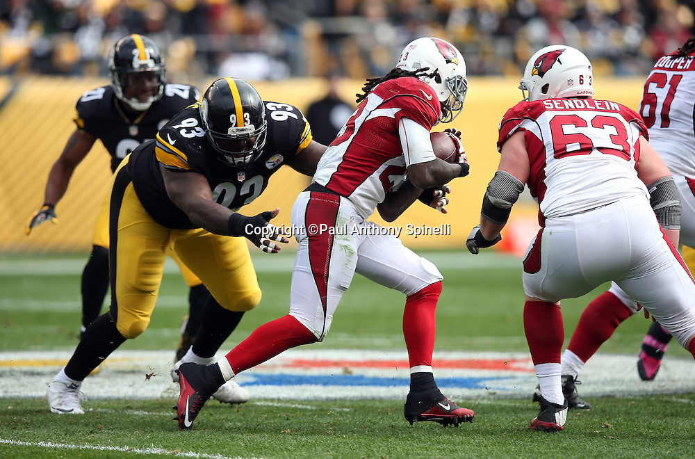 Arizona Cardinals center Lyle Sendlein (63) looks on as Arizona Cardinals running back Chris Johnson (23) runs for a first quarter gain of 8 yards while Pittsburgh Steelers defensive end Cam Thomas (93) gives chase during the 2015 NFL week 6 regular season football game against the Pittsburgh Steelers on Sunday, Oct. 18, 2015 in Pittsburgh. The Steelers won the game 25-13. (©Paul Anthony Spinelli)