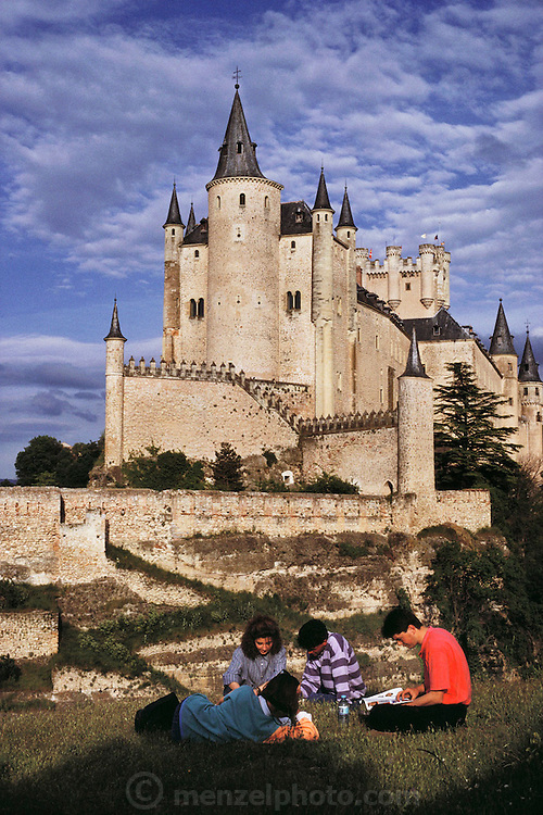 Alcazar de Segovia, Spain with four teens in the foreground reading.