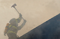 Gloucester: Gloucester firefighter Charlie Scola, tries to break through the roof the Riverview Road housefire yesterday morning. ((((note to imaging: please don't increase the contrast in this picture too much -it's supposed to be a little muddy/smokey)))))))   (Photo by Mike Dean/Gloucester Daily Times). Wednesday, January 29, 2003 (NOTE: THIS IS A DIGITAL CAMERA IMAGE)..**************************************.Filter: Min (QMPro: Red Radius:0/Blue Radius:3/No Desp.).USM: Normal (Amt:200/Radius:0.3/Thresh:2).File Size: 7.34MB.Original file name: DSC_2224.JPG