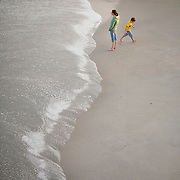 People walk and play near the waves at Wrightsville Beach, NC...