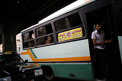 A ticket collector stands on the doorway of a Cairo bus.