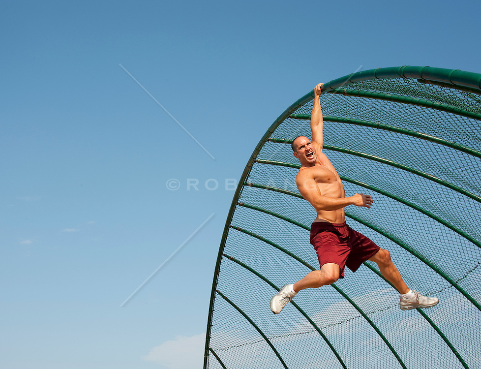 Young athletic man hanging from a fence