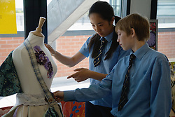 Secondary school students looking at a dress maker's mannequin in an art lesson,