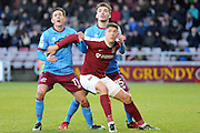 Alex Revell of Northampton Town holds back Josh Morris of Scunthorpe United and Harry Toffolo of Scunthorpe United during the EFL Sky Bet League 1 match between Northampton Town and Scunthorpe United at Sixfields Stadium, Northampton, England on 14 January 2017. Photo by Andy Handley.