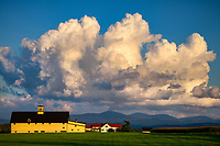 Huge cumulous clouds and late day light over a picturesque barn and farm in Vermont, USA