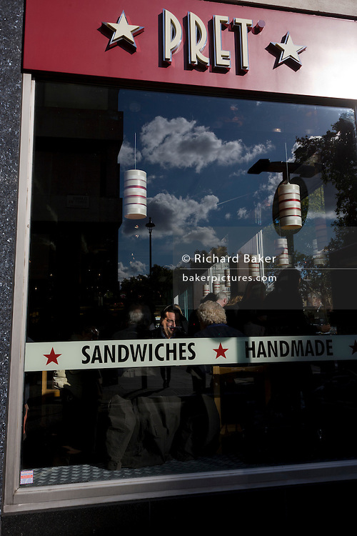 Lunchtime diners see through a window of successful sandwich chain Pret a Manger in central London.