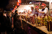 Boys eat candied strawberry sticks from stall in the Night Market, Wangfujing Street, Beijing, China