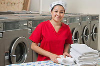 Portrait of a Hispanic female employee with towel in Laundromat