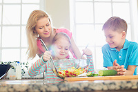 Family looking at girl mixing salad in kitchen