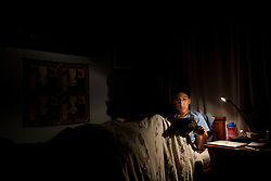 """Santiago Gonzalez, 13, reads a programming text book in bed before falling asleep, Littleton, Colo., Aug. 29, 2011. Gonzalez is a full-time college student at the Colorado School of Mines, an engineering university. He wakes up at 5:30 a.m. every morning during the academic semester to develop iPad and iPhone applications in a programming language called Objective C, which he learned from a textbook when he was 9 years old. That textbook and 86 similar volumes including Applied Finite Mathematics, Infinity in Your Pocket, Programming in C++ and Dictionary of Physics, sit in a glass-fronted bookcase opposite his bed. """"Exceptionally gifted"""" is the commonly used phrase for kids as smart as Gonzalez."""