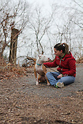 December 8, 2013 - Brooklyn, NY. Valerie Greenblatt, a volunteer at Sean Casey Animal Rescue, enjoys a moment in the park with her own adopted pitbull, Trixie. Trixie was found in a sewer with severe eye infections that left her blind before she was taken in by Sean Casey's shelter. 12/8/2013 Photograph by Nathan Place/NYCity Photo Wire
