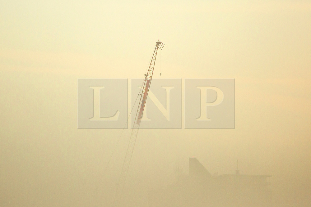 © Licensed to London News Pictures. 20/09/2015. Leeds, UK. Picture shows a crane rising from the fog this morning. The city of Leeds woke this morning to a thick blanket of fog which is expected to clear to a mostly dry clear day..Photo credit: Andrew McCaren/LNP
