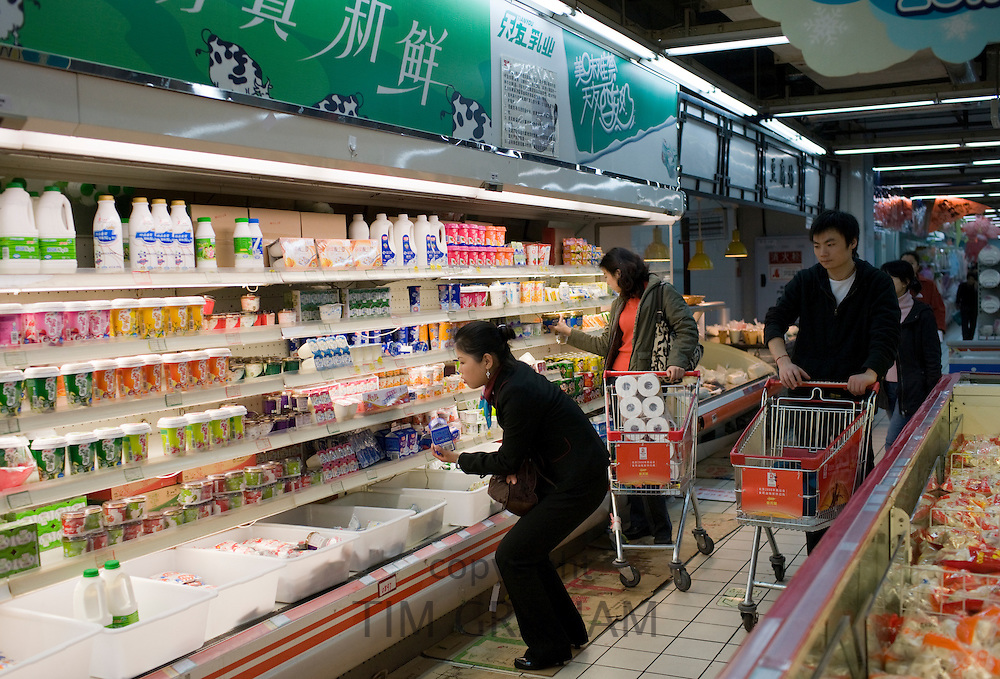 People with shopping trolleys buying goods in supermarket in Chongqing, China