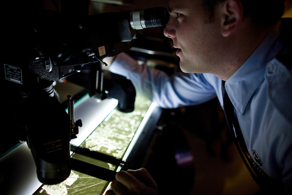 Geospatial Intelligence Analyst Airman First Class James Lowe examines film shot from a U2 at Beale Air Force Base February 24, 2010 in Linda, Calif.