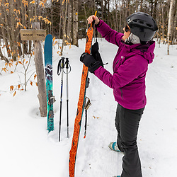 A woman puts skins on her skis before heading up a trail at Loon Echo Land Trust's Bald Pate Mountain Preserve in South Bridgton, Maine.