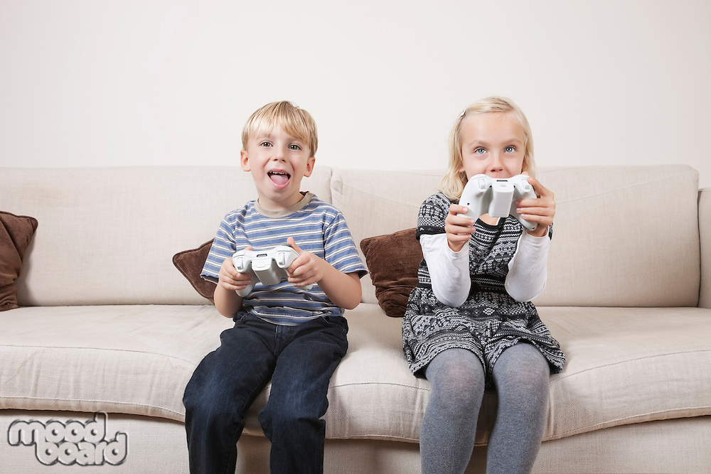 Happy brother and sister playing video game on sofa
