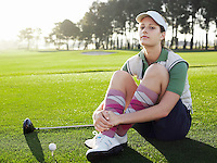 Young female golfer sitting on court portrait