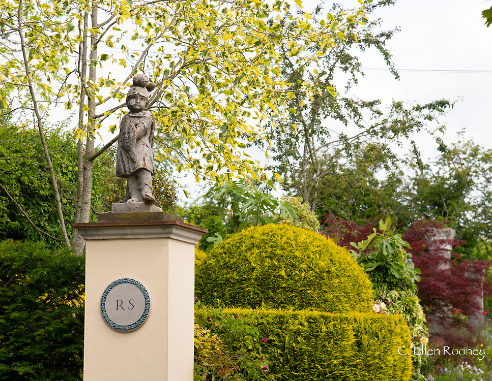 A pillar, stone statue and Cypress topiary globe at the entrance to the Laskett Gardens, Much Birch, Herefordshire, UK