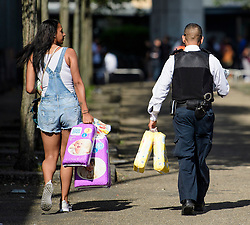 © Licensed to London News Pictures. 15/06/2017. London, UK. A policeman helps residents carry donated nappies the day after the a huge fire at the Grenfell tower block in west London. The blaze engulfed the 27-storey building killing 12 - with 34 people still in hospital, 18 of whom are in critical condition. The fire brigade say that they don't expect to find anyone else alive. Photo credit: Ben Cawthra/LNP