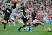 Jordan Henderson tackles Charlie Adam during the Barclays Premier League match between Stoke City and Liverpool at the Britannia Stadium, Stoke-on-Trent, England on 9 August 2015. Photo by Alan Franklin.