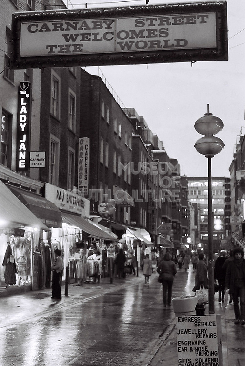 "Carnaby Street London, December 1981 with ""Carnaby Street welcomes the world"" sign. London, Soho, UK, 1981."