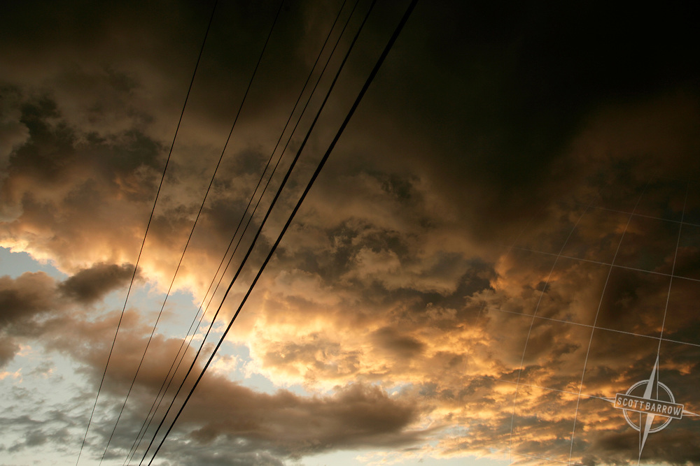 Storm clouds at sunset. Power lines.