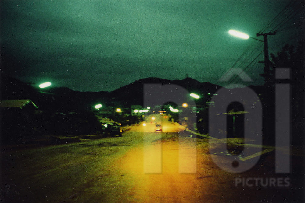Road through a mountain town lit by streetlights, Northern Laos, Southeast Asia
