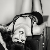 Woman in black and white on drawer with laced underwear and tattoos with seductive expression