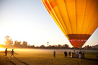 A hot air balloon prepares to take off in the early morning sunrise in Napa, California