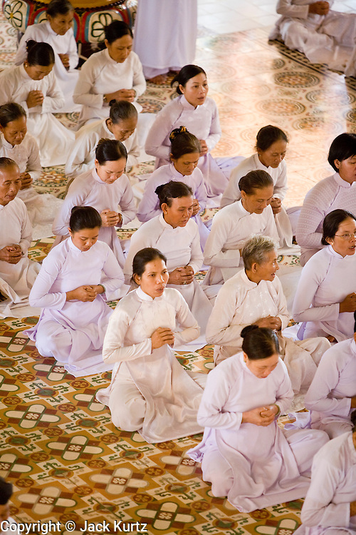 "10 MARCH 2006 - TAY NINH, VIETNAM: Noon prayers at the Cao Dai Main temple in Tay Ninh. The Cao Dai complex in Tay Ninh is the sect's headquarters. The Cao Dai religion is a blending of Buddhism, Confucianism, Taoism, Christianity and Islam. There ""saints""  include Chinese leader Sun Yat Sen and French author Victor Hugo. There are about two million members of the Cao Dai religion in Vietnam. British author Graham Greene, who wrote about the Cao Dai in the ""The Quiet American"" said the relegion was ""a Walt Disney fantasia of the East."" Photo by Jack Kurtz / ZUMA Press"