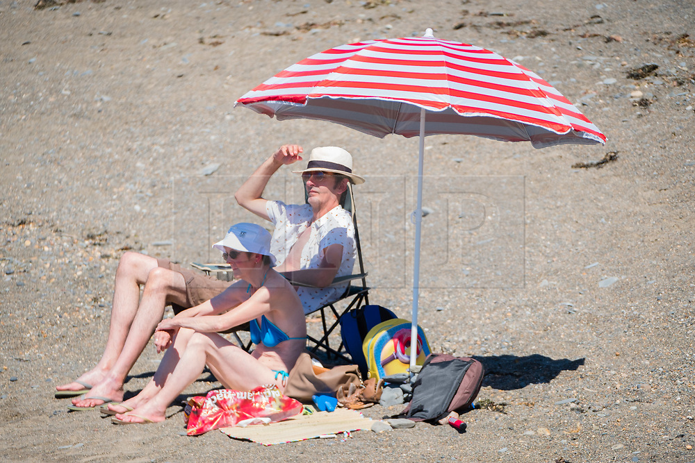 © Licenced to London News Pictures<br /> 26 June 2018 . Aberystwyth Wales UK<br /> <br /> UK Weather:  On another scorchingly hot day at the seaside in Aberystwyth, people flock to the beach and sea to top up their tans and cool down  a little in the clear shallow  waters of Cardigan Bay<br /> The UK is in the grips of a mini heatwave, with temperatures widely  forecast to reach over  30º Celsius in many parts of the country<br /> photo CreditKeith Morris / LNP